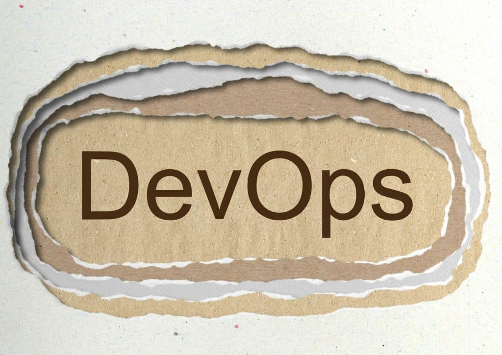 DevOps - word in ragged paper hole background -software development and information-technology operations - concept tattered illustration